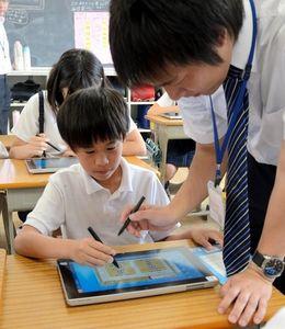 写真:担任からタブレットパソコンの使い方を教わる児童=草津市西渋川2丁目の市立渋川小学校