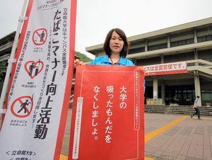 写真:禁煙の啓発ポスターを持つ立命館大学の職員=北区