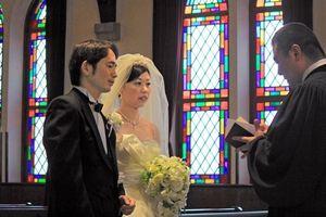 写真:ステンドグラスが印象的な同志社大の礼拝堂で、結婚式のリハーサルに臨む新郎と新婦=上京区