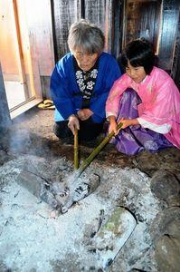 写真:灰をかけて火を消す火焚き乙女の山部慈さん(右)=阿蘇市役犬原