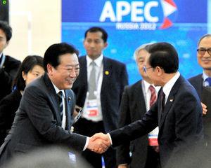 写真:APEC首脳会議を前に韓国の李明博大統領(右)と握手する野田佳彦首相。アルファベット順の席次のため、隣同士になった=8日午後3時37分、ロシア・ウラジオストク、仙波理撮影