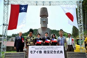 写真:白サンゴと黒曜石でできた瞳がはめこまれたモアイ像を背景に記念撮影をする関係者たち=25、宮城県南三陸町、日吉健吾撮影