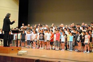 写真:公演に向けて、指揮者の大友直人氏に指導を受ける花巻市民らの合唱団=花巻市文化会館