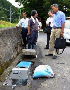 写真:側溝には小水力発電が設置され参加者の関心を集めていた=遠野市土淵町の米通集落