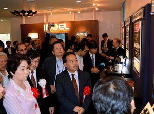 写真:山形大有機エレクトロニクスイノベーションセンターの展示コーナーを見学する吉村知事(左)ら=米沢市アルカディア