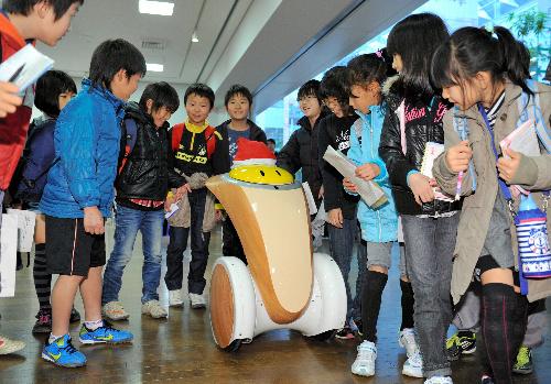 写真:実証実験中のツアーガイドロボットと一緒に歩く小学生たち=7日午前、愛知県常滑市の中部空港、福留庸友撮影