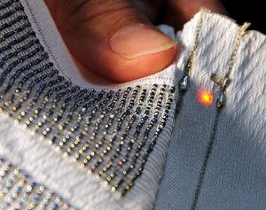 写真:直径1.2ミリの球状太陽電池がずらりと織り込まれた繊維。小型LEDが点灯した
