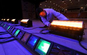 写真:スタッフが触れているのが歌舞伎座に設置されるLED照明。手前はカラーフィルムを貼った従来のハロゲン照明=16日、山梨県市川三郷町、遠藤真梨撮影