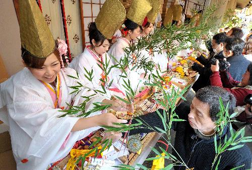 写真:福娘から福笹に縁起物を付けてもらう人たち=9日午前、大阪市浪速区の今宮戎神社、高橋一徳撮影