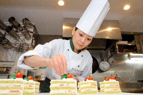 写真:小松菜とミニトマトを用いたケーキ「グリーンショート・トマト」を作る柿沢安耶さん=東京都目黒区、瀬戸口翼撮影