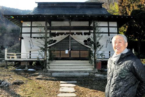 写真:岡地天満宮の前に立つ、稲玉浩政さん。「参拝者が増えてうれしいです」=千曲市