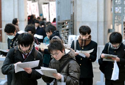 写真:受験番号と会場地図を見比べて、センター試験の会場を確認する受験生たち=19日午前8時21分、東京都文京区の東京大学、加藤諒撮影