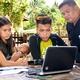 バスケットボールの屋外コートで、ノートパソコンの映像授業を受ける生徒たち。赤ん坊を抱いた女子もいた=フィリピン南部カミギン島、伊東和貴撮影