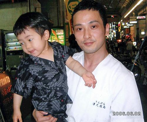写真:父の俊作さんに抱かれる悠貴徳君=2006年6月撮影、片山恵津子さん提供