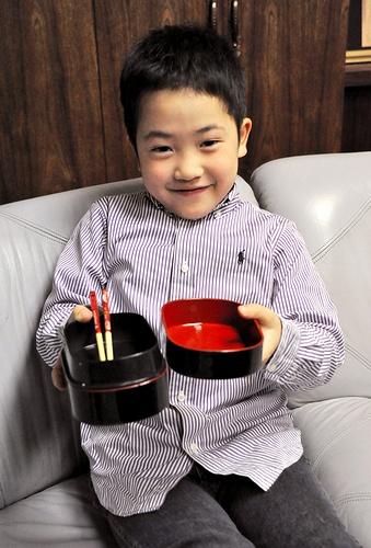 写真:お父さんの弁当箱を持つ悠貴徳君=広島市中区