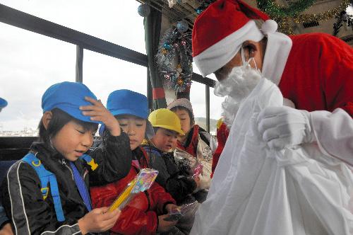 写真:サンタにプレゼントをもらう園児たち=甲賀市の信楽高原鉄道