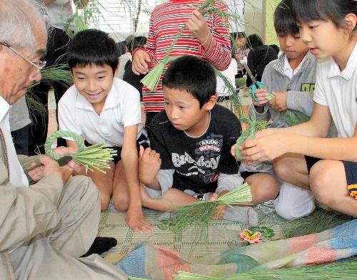 写真:小学生にしめ縄づくりを教える大門しめ縄組合の組合員(左)=岡崎市大門4丁目