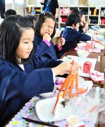写真:器用にカニの身を食べる児童たち=兵庫県香美町香住区香住