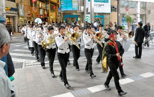 写真:天文館周辺を演奏して歩く高校生たち=鹿児島市中町
