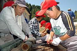 写真・高辻会長(左)の指導で竹コップを作る小学生=田布施町下田布施