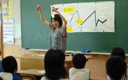 写真・挫折と栄光を示したグラフの前で、世界陸上のメダルを児童に披露する千葉真子さん=一関市立萩荘小学校