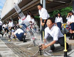 写真・手作りの水ロケットを飛ばす生徒たち=大津市瀬田南大萱町