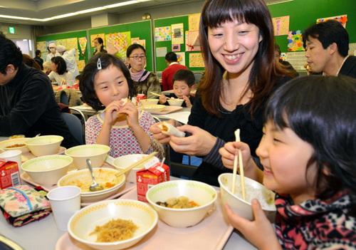 写真:おいしそうに給食を食べる新1年生と保護者=福岡市中央区舞鶴2丁目