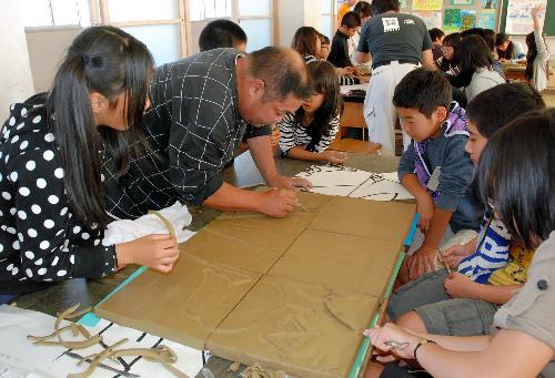 写真:鬼師と呼ばれる職人から陶板づくりの指導を受ける児童たち=高浜市立港小学校