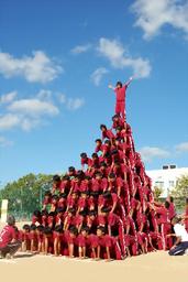 写真:一番上に乗った生徒が両手を広げ、10段ピラミッドが完成=9月25日、兵庫県伊丹市鴻池3丁目、市立天王寺川中学校提供