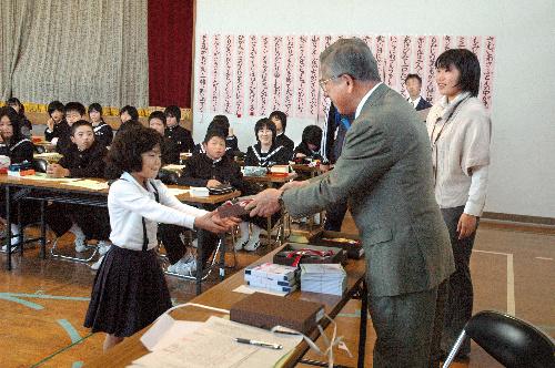 写真:俳句大会で特選になり、和田さんから盾を受け取る村上さん=福山市加茂町北山の広瀬中学校体育館