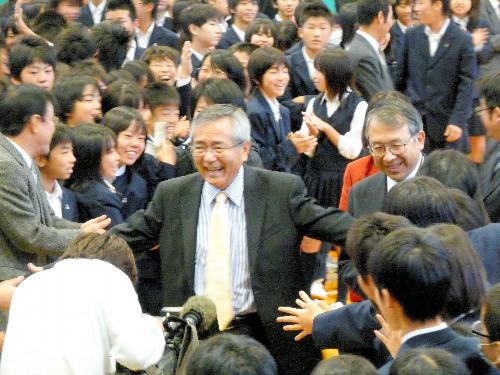 写真:母校・大和市立大和中学校の生徒たちに歓迎されながらスピーチの壇上にのぼる根岸英一さん