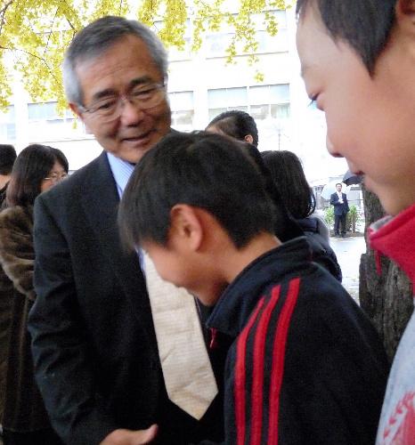 写真:出身校・大和市立大和小学校の思い出のイチョウの木の下で後輩たちと握手する根岸英一さん(左)