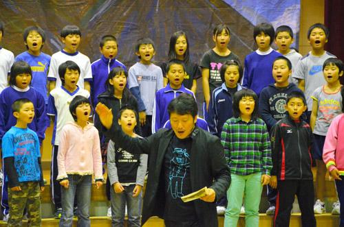 写真:岩村力さん(中央)の指揮で合唱する児童たち=岩手県大船渡市立甫嶺小学校、山西厚撮影