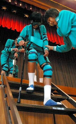写真:視野を狭めるゴーグル、腰がかがむベルトを付けて階段下りを体験する中学生=船橋市七林町