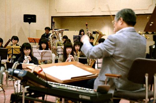 写真:バンドミュージックキャンプで井田重芳理事長(右)の指導を受ける高校生たち=札幌市中央区