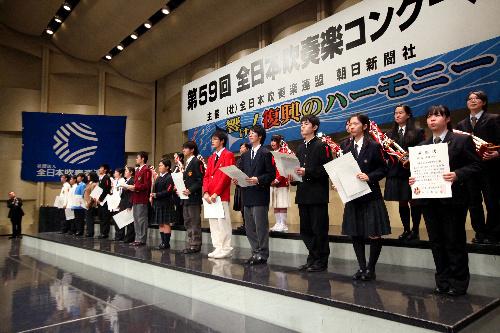 写真:表彰式で「響け!復興のハーモニー」と書かれた横断幕を背に並んだ各校の生徒たち=23日午後、東京都杉並区の普門館、金子淳撮影