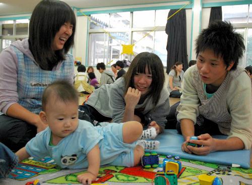 写真:赤ちゃんと対面し、関心を引こうと工夫する高校生たち=千葉県鎌ケ谷市の県立鎌ケ谷高校