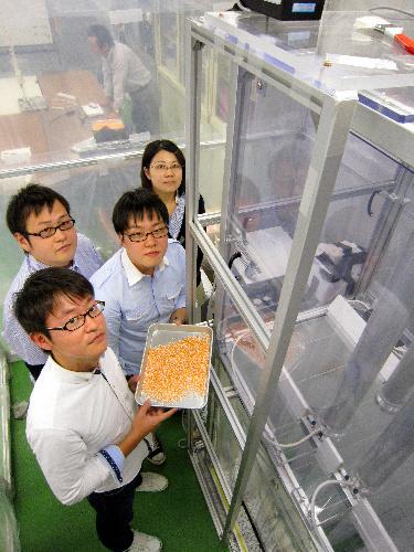 写真:芝浦工大:実験装置の前で細かく砕いたプラスチック片を手にする芝浦工業大の学生たち=東京都江東区