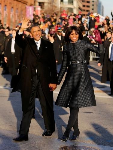 写真:就任式後のパレードで聴衆に手を振るオバマ米大統領とミシェル夫人(右)=ロイター
