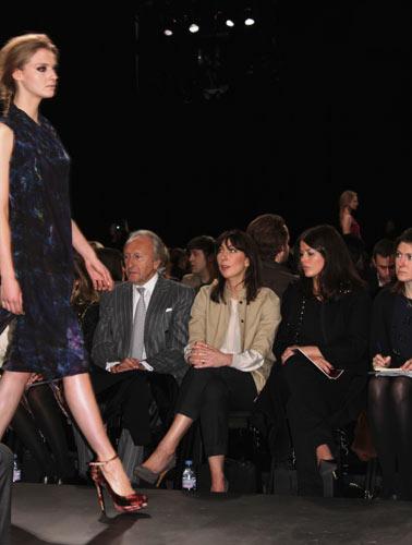 写真:ベージュのコートに黒のクロップドパンツを合わせたサマンサ・キャメロン首相夫人(中央)。左は、英国ファッション・カウンシルのハロルド・ティルマン会長(左)