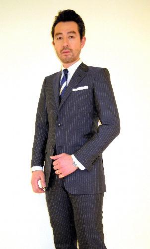 カラー写真:宮崎俊一バイヤー。着用しているのは、全工程を1人の職人が縫い上げた「丸縫い既製スーツ」=松屋銀座提供