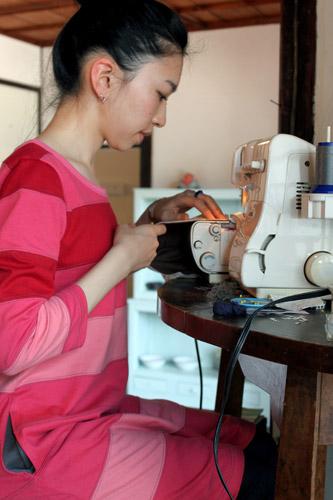 写真:生地選びが終わったら、その場でミシンで縫い合わせる。約5分で完成品に=高松市内のギャラリー「NISHI NISHI」、竹端写す