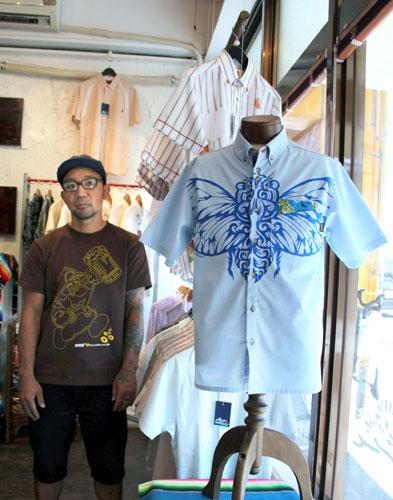 写真:スターテックスのクマゼミ柄かりゆしウエア。左はデザイナーの玉木真次郎さん=沖縄県北谷町
