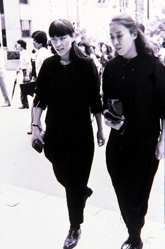 写真:全身黒ずくめの「カラス族」。この2人は「ハウスマヌカン」と呼ばれたDCブランドの販売員風=1981年、渋谷、アクロス編集部提供