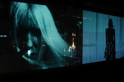 写真:アグリ・サギモリ(AGURI SAGIMORI)。映像を映すガラス窓の向こうに、現物のドレス(中央)が浮かび上がる