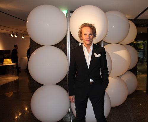 写真:キュレーターのイルカ・スッパネン氏。今展示のシンボルである風船(後方)は「フィンランドの雪、閃きを表す泡を示しています」。