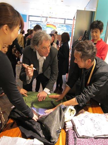 写真:ブティックで、お客さんのジャケットにサインをするポール・スミス。サプライズでの登場に、店内は沸いた=4月9日、東京・丸の内で 同社提供