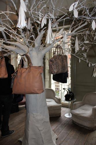 写真:紙で出来た木の枝に、大きなタッセルやバッグがつり下げられていた
