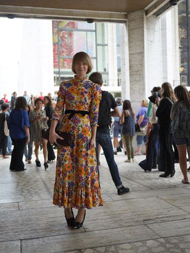 写真:ボリューム感のあるドレス・ワンピースも華やかな花柄で着こなして。ベルトと靴とバックの黒色で全体を引き締めている