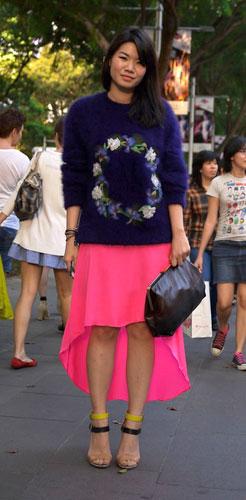 写真:蛍光ピンクのスカートは後ろがロングで前は膝丈のアシンメトリー型になっている。灼熱の太陽の中、LANVINのニットセーター(!)がファッションへの気合いを感じさせます。